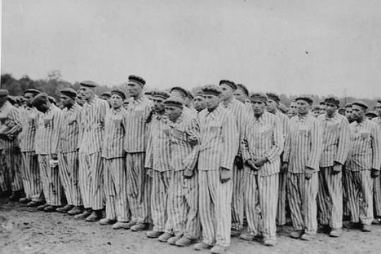 "Prisoners standing during a roll call. Each wears a striped hat and uniform bearing colored, triangular badges and identification numbers. *""Buchenwald, [Thuringia] Germany, 1938-1941. [http://www.ushmm.org/ United States Holocaust Memorial Museum]"