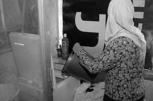 The water is shut off, the electricity is still running. This is how you get the laundry machine to work with no running water, Jaffa, September 2014. (Photo by Yudit Ilany)